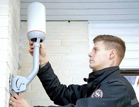 Asentaja Petri Saari kiinnittää ulkomokkulaa talon seinään Vantaalla. DNA testaa omakotitaloalueella kiinteää langatonta yhteyttä.