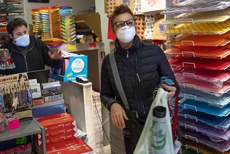 Kaupan työntekijä ja asiakas suojasivat itsensä hengityssuojaimella tiistaina Roomassa Italiassa.
