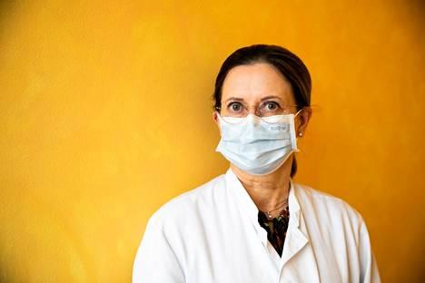 Kasvomaskin käyttö voi monissa tapauksissa ehkäistä koronaviruksen leviämistä. Ylilääkäri Jaana Syrjänen näyttää mallia.