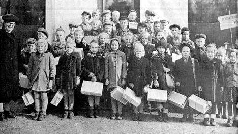 Tässä Valokuvaamo Nurmisen ottamassa kuvassa poseeraavat Mäntän Mäkikylän koulun oppilaat opettajansa Esteri Koivumäen ja puukenkälaatikoiden kanssa 1940-luvulla. Kuvan on toimitukseen lähettänyt Lyyli Lamminen, jonka poika Kalevi  on myös ensiluokkalaisena kuvassa.
