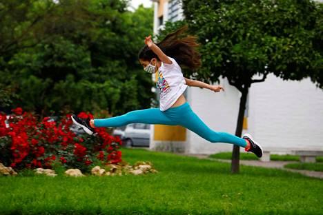Espanjalainen tyttö pomppi Cordobassa kadulla kasvomaski suojanaan päästyään sunnuntaina ulos ensimmäistä kertaa kuuteen viikkoon.