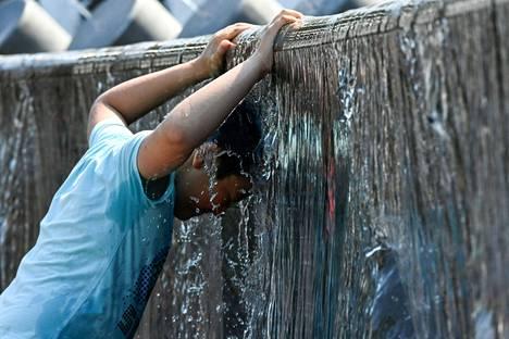 Poikkeuksellisen lämmin sää pakotti venäläisen nuorukaisen viilentämään itseään suihkulähtessä Moskovassa heinäkuun puolivälissä. Helteitä on koettu eri puolilla maailmaa tänä kesänä.