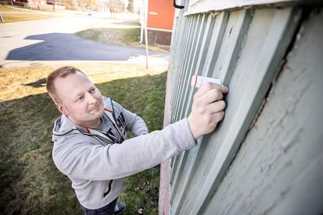 VäriÄssien asiantuntija Jani Koivunen mittaa seinän ulkopinnasta Tikkurilan ColorReaderilla, mikä talon nykyinen pintamaalin sävy on.