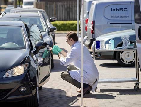 Työntekijä keräsi Hollannissa autoilijoilta keskiviikkona näytteitä covid-19-taudin vasta-ainetestiä varten.