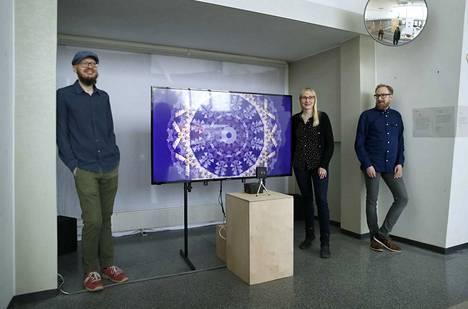 """Porilainen taiteilijaryhmä {TES} yhdistää taidetta ja tekniikkaa vaikuttaviksi, algoritmisiksi teoksiksi. Kolmikkoon kuuluvat Sami Luusalo (lippalakissa), Tea Söderlund ja Eetu Henttonen. Porin vanhalla linja-autoasemalla on esillä heidän teoksensa """"Kriittinen etäisyys"""", joka muuttuu katsojan lähestyessä teosta tai etääntyessä siitä."""