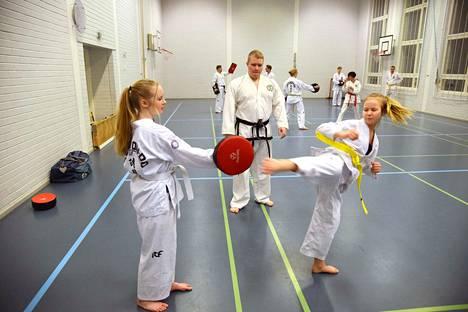 Laura Virtanen ja Sanni Harju harjoittelivat keskenään potkutekniikoita tiistaina Kärjenniemen koulun salissa. Valkeakosken Taekwondon opettaja Larjus Lamponen seurasi silmä tarkkana.
