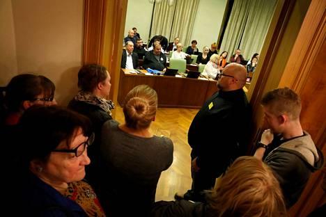 """Runsas yleisö seurasi kaupunginvaltuuston kokousta oviaukosta 26. helmikuuta 2018, kun tuulivoimakaavasta päätettiin. Satakunnan Kansa kertoi tuolloin, että """"lähes sata ahlaislaista täytti Porin valtuustosalin aulan ja kahviosalin""""."""