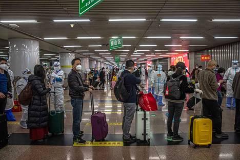 Wuhanista saapuneet matkustajat jonottivat bussiin pääsyä Pekingin rautatieasemalla keskiviikkona. Heitä odotti kahden viikon karanteeni joko hotellissa tai kotonaan.