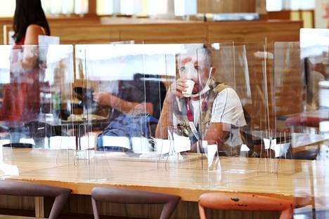 Mediatyöläinen kahvitauolla eristyskopissaan.