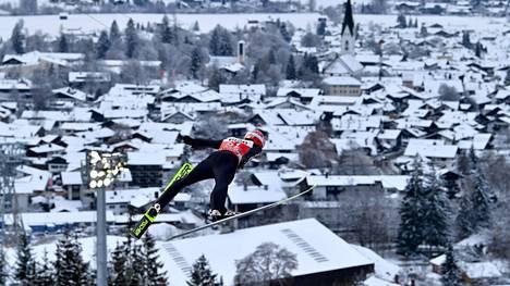 Oberstdorf isännöi MM-hiihtoja noin kuukauden kuluttua. Kuvassa hyppää saksalainen Markus Eisenbichler ja taustalla siintää kisapaikkakunta.