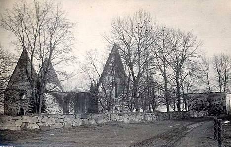 Sääksmäen kirkon rauniot huhtikuun alussa 1929. Kirkosta oli pystyssä vain kiviset seinät. Lohduttomasta näkymästä on kulunut 90 vuotta. Kirkon puissa istuvat naakat surevat menetettyä asuinpaikkaansa. Oikeassa reunassa näkyy kellotapulin kivinen alaosa.