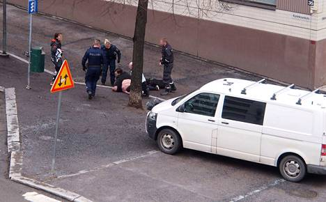 Kuvassa näkyy, miten kiinniotettu henkilö oli poliisien ja järjestyksenvalvojien ympäröimänä maassa ilman paitaa.