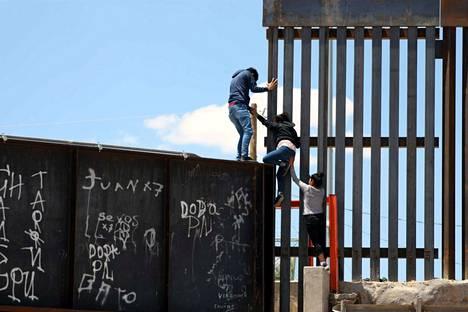 Joukko ihmisiä yritti päästä muurin yli Meksikosta Yhdysvaltojen puolelle heinäkuussa 2019. Rajamuurihankkeesta on tullut presidentti Donald Trumpin tiukan maahanmuuttopolitiikan symboli.