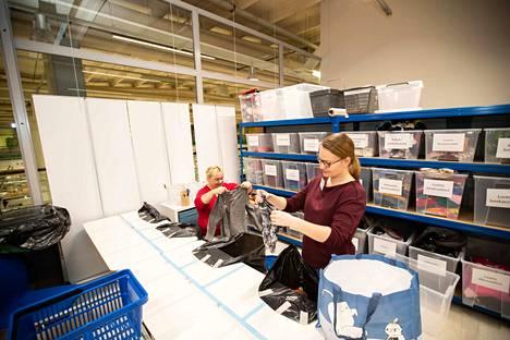 Merja Hassinen ja Laura Rantakoivu lajittelevat lahjoitusvaatteita.