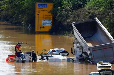 Pelastustyöntekijöitä tulvivalla kadulla Saksassa lauantaina.