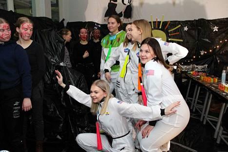 Avaruusaiheisen luokan nuoret naiset poseeraavat.