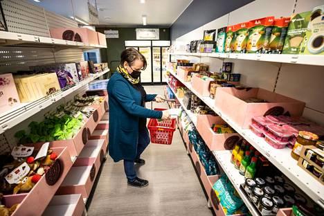 Tampereen ev. lut. seurakuntien uuden hävikkiruokakaupan hyllyillä on jo kuivatavaraa, esittelee elintarvikeavun koordinaattori Marja Palkonen.