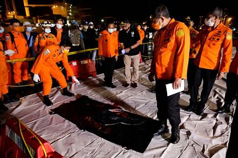 Indonesian viranomaiset tutkivat laukkua, jossa uskotaan olevan koneen jäänteitä.
