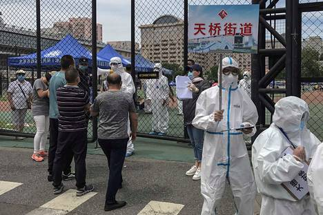 Pekingiläisen ruokatorin lähialueiden asukkaat jonottavat koronavirusterstiin.