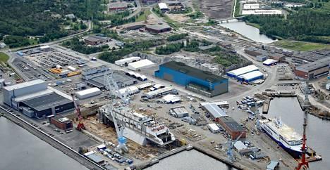 Telakan uusi monitoimihalli havainnekuvan keskivaiheilla. Halli erottuu sinisellä julkisivullaan muista meriteollisuuspuiston rakennuksista.