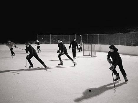 Heska Korhosen maanantai-iltana 11.1. ottamassa kuvassa nuoret miehet pelaavat höntsäkiekkoa lumisella Roukon kentällä.