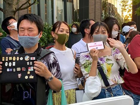 Japanilaiset tervehtivät kadun varrella, kun toimittajia marssi avajaisiin.