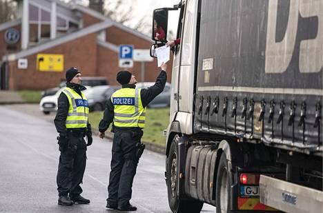Saksan poliisi tarkastaa kuorma-auton kuljettajalta asiakirjoja Tanskan rajalla. Tanska on sulkenut liikenteensä ulkomaalaisten matkustamiselta. Nyt koko Schengen-Euroopan ulkorajojen sulkemista harkitaan.