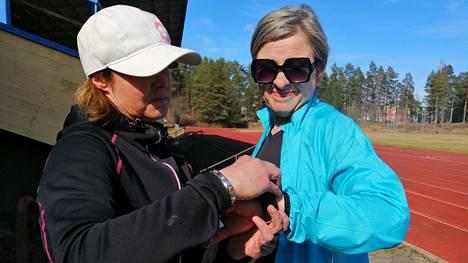 Heli Peltola asettelee sykemittaria Kirsi Lankisen ranteeseen ja antaa ohjeita testikävelyyn.