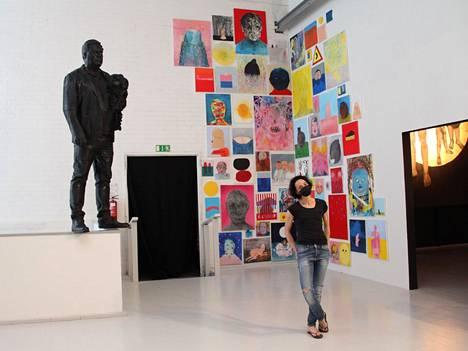 Kuraattori Anna Ruth esitteli keskiviikkona näyttelyä medialle. Vasemmalla Jaakko Himasen ja Vesa Toukomaan 3D-tulostuksella tehty Monumentti, takana Tiitus Petäjäniemen maalauksia. Oikealla huoneesta näkyy hieman Mariam Hajin maalausta.