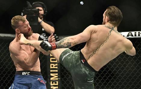 Tyrmäyskone Conor McGregor (oikealla) antoi jalkansa puhua. Donald Cerronen paketti hajosi totaalisesti tämän yläpotkun seurauksena.
