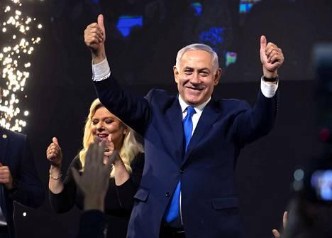 Oikeistolainen Benjamin Netanjahu näyttää jatkavan Israelin pääministerinä parlamenttivaalien jälkeen. Taustalla on vaimo Sara Netanjahu.