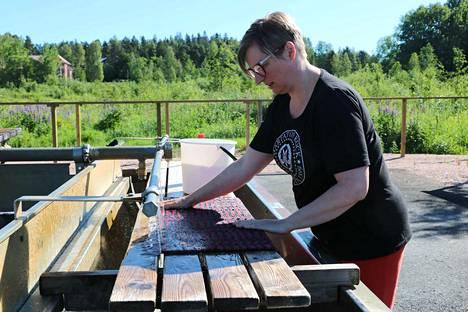 """Etelä-Hämeen marttojen kotitalouden asiantuntija Niina Mäkelä toteaa, että mattoja pestessä on hyvä olla mukana pesutarvikkeiden lisäksi juomavettä, hattu ja aurinkorasvaa. """"Ja jos mahdollista, on hyvä laittaa uikkarit päälle, sillä tässä kastuu"""", Mäkelä vinkkaa."""