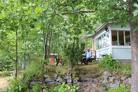 Jukka Matinlinnan on mukava nauttia kahvikupponen mökkitontin ylätasanteella kymmenien puulajien ympäröimänä.