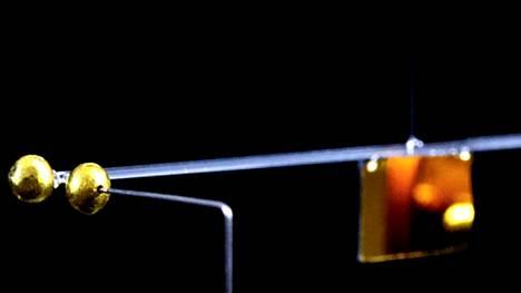 Kultapallojen vetovoiman voi mitata siitä, miten paljon vaaka kiertyy.