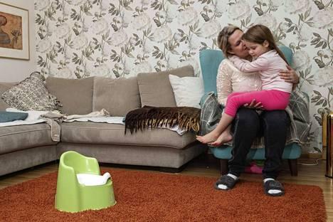 Äidin Tytti Artkosken sylissä istuva Kerttu on sopeutunut siihen, että hänellä on vaikea suolistosairaus ja hän tietää, miten taudin kanssa eletään.