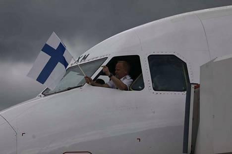 Leijonat ovat saapuneet Suomeen. Lentokoneen kapteeni heilutti lippua lentokoneen ikkunasta.
