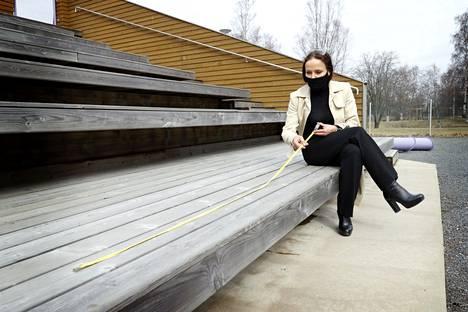 """Maria Kuusiluoma mittasi Kirjurinluodon kesäteatterien penkkejä turvallisten etäisyyksien arvioimiseksi. Teatteri aikoo esittää näytelmän """"Iloisia aikoja, Mielensäpahoittaja"""", vaikka yleisörajoituksia kesäkuulle tulisikin."""