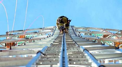 Asentaja Marko Hynninen kipuaa kohti taivasta jopa 40 metrin korkeuteen. Sähkötolppien korkeus vaihtelee maaston mukaan.
