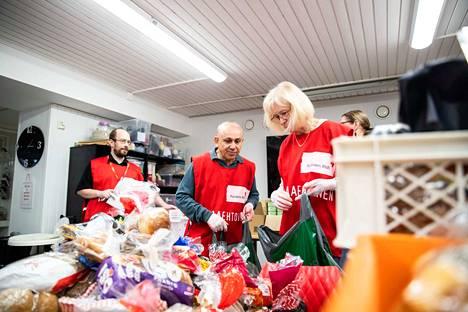 SPR:n ruoka-apujono työllistää myös vapaaehtoisia.  Petri Huuhkanen, Hamdi Uldag ja Carita Hjorth pakkasivat ruokakasseja Otavalankadulla.