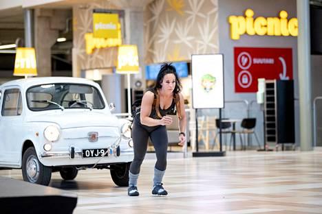 Pirita Ruusulaakso yrittää vetää kymmentä Fiat 500 -autoa kauppakeskus Puuvillassa.