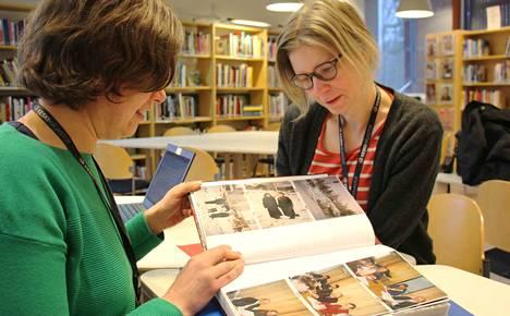 Hanne Rokkonen ja Johanna Hämäläinen muistelevat kirjaston historiaa valokuva-albumin äärellä.