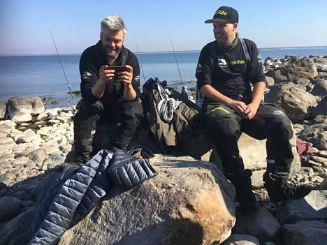 Yrittäjät Olli ja Jaakko Ojamo mielipuuhissaan: kalastamassa ja kännykkää näpräämässä.