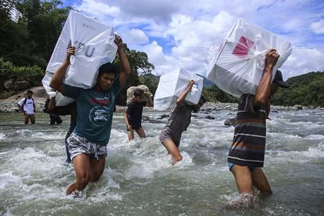 Vaalivirkailijat kantoivat äänestysuurnia joen yli jotta ihmiset pääsivät äänestämään Etelä-Sulawesin kaukaisissa kylissä Indonesiassa 16. huhtikuuta.