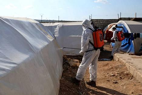 Vapaaehtoiset desinfioivat telttoja pakolaisleirillä Idlibin maakunnassa. Koronaviruksen leviäminen ahtailla pakolaisleireillä voi johtaa katastrofiin.