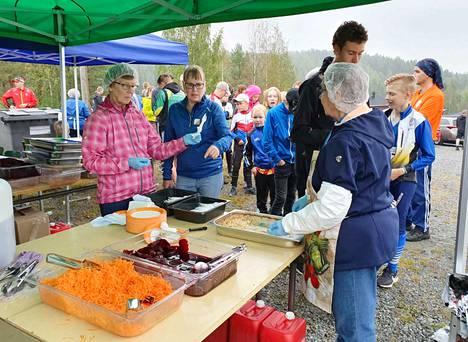 Kinkkukiusauksen kanssa tarjolla on porkkanaraastetta ja punajuuriviipaleita. Ruokateltalla palvelevat Marja-Leena Nokelainen, Sirpa Mörsky ja Marja-Leena Korpinen.