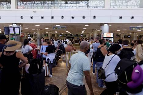 Kohti kotia ja muuttuneita suunnitelmia: Turistit seisoivat kahdessa pitkässä check in -jonossa Teneriffan Surin lentoasemalla sunnuntaina sen jälkeen, kun Britannia ilmoitti ottavansa käyttöön paluukaranteenin Espanjan kasvavien koronalukujen takia.