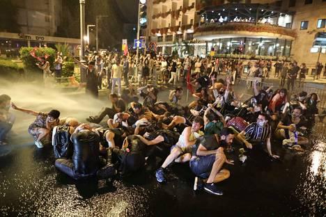 """Netanjahu on nuhdellut mielenosoittajia ja tviitannut: """"älkää kiskoko maata kohti anarkiaa, väkivaltaa ja hyökkäyksiä poliiseja vastaan"""". Israelin poliisi käytti vesitykkiä mielenosoittajiin, jotka tukkivat tien osoittaessaan mieltä heinäkuun puolessavälissä Jerusalemissa Israelissa."""