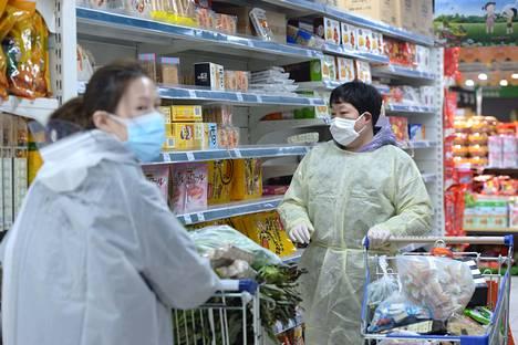 Wuhanilaisessa marketissa asiakkaat pyrkivät suojautumaan virustartunnalta hengitysmaskien lisäksi muovisin takein.