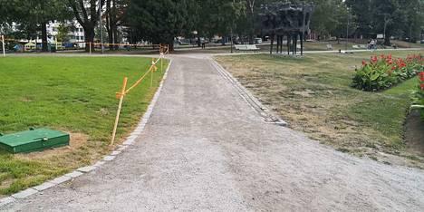 Koskipuistossa ruoho on vihreämpää aidan takana.
