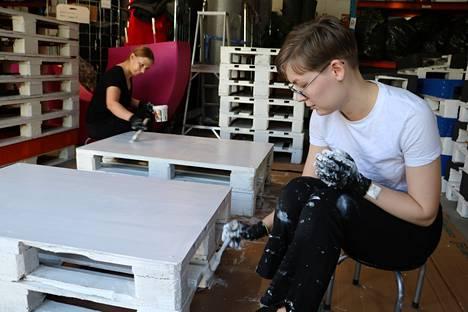 Terhi Lehtola ja Mirja Karjalainen maalaavat kuormalavoista rakennettuja pöytiä.